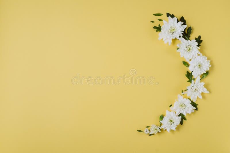 idérik blommasammansättning Krans som göras av vita blommor på gul bakgrund Moderdag, kvinnors dag, vårbegrepp arkivbilder