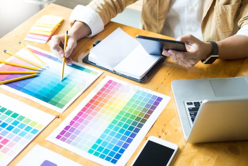 Idérik grafisk formgivare på arbete Palett för pantone för färgprovkartaprövkopior i det moderna kontoret för studio, inredesign, arkivfoto