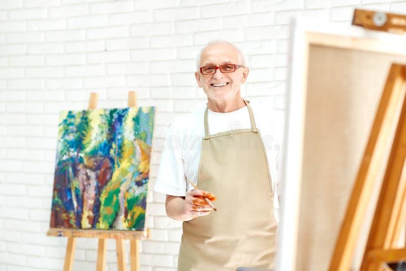 Idérik hög målare som drar färgrik abstrakt målning på den ljusa studion arkivfoto