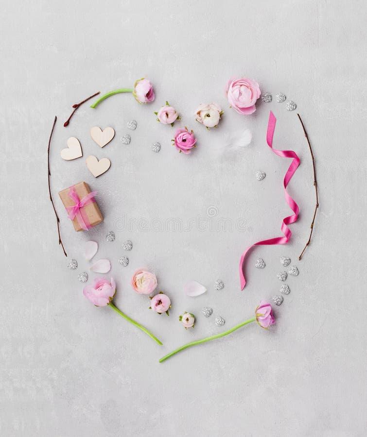 Idérik hjärta i flatlay stil som göras från blommor, gåvan och garneringar på grå färgstentabellen från ovannämnt för valentindag royaltyfri foto