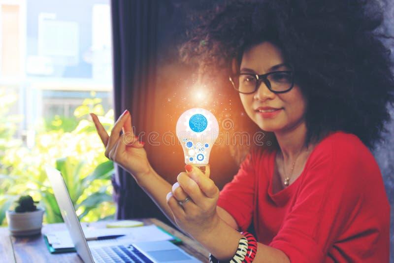 Idérik idé och innovationbegrepp, affärskvinnahand som rymmer den ljusa kulan med hologrammet i inrikesdepartementet royaltyfri fotografi