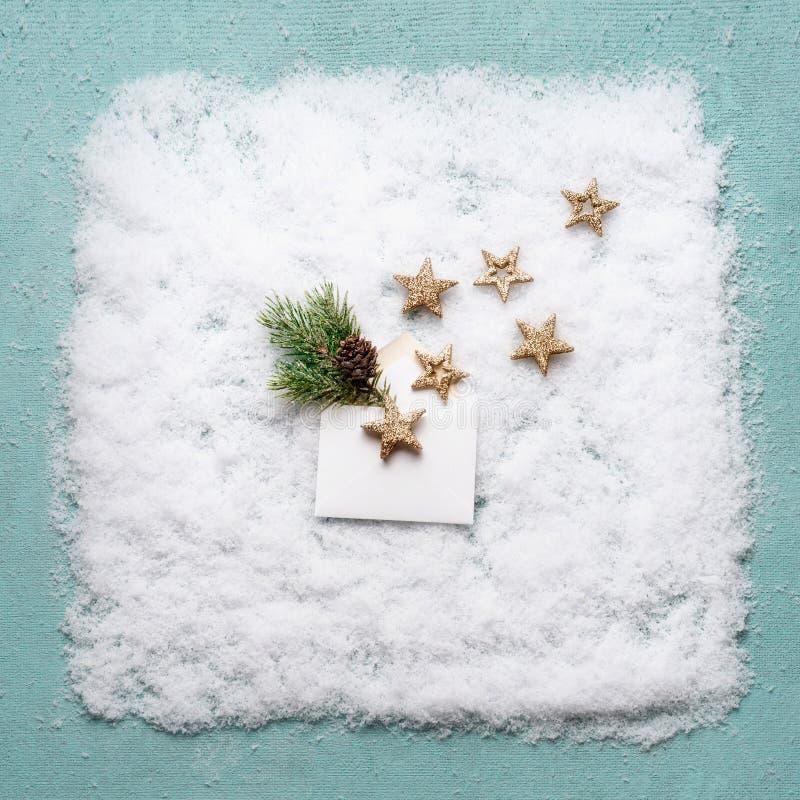 Idérik julsammansättning med det öppna kuvertet med guld- stjärnor och granfilial i snö på blå bakgrund, bästa sikt royaltyfria foton