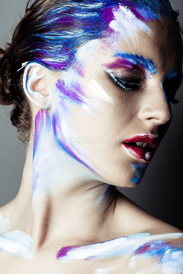 Idérik konstmakeup av en ung flicka med blåa ögon arkivfoto
