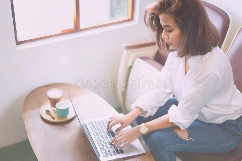 Idérik kvinna som skriver hennes bärbar dator för att arbeta arkivbilder