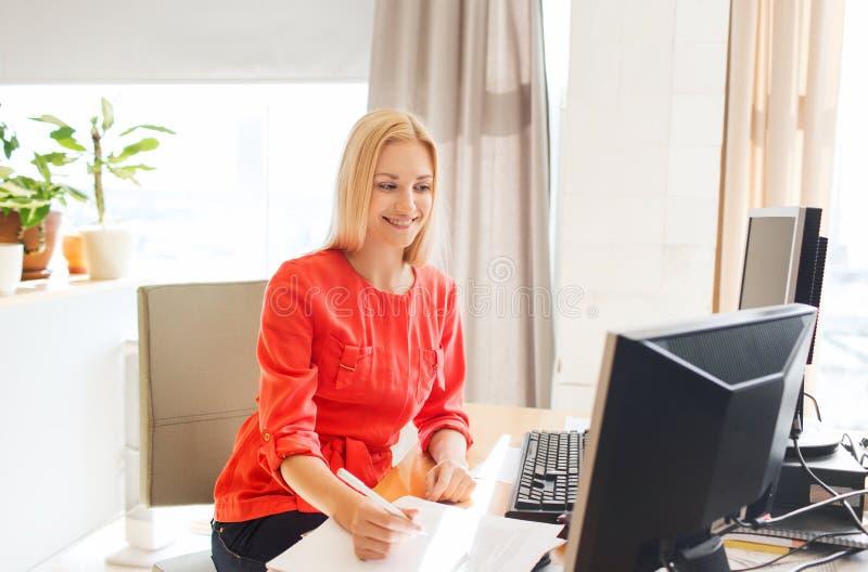 Idérik kvinna som skriver till anteckningsboken på kontoret arkivfoton
