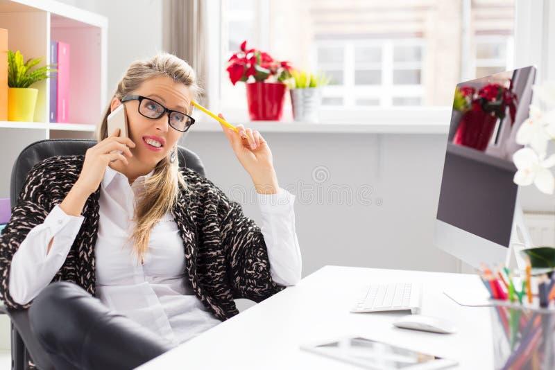 Idérik kvinna som talar på telefonen, medan sitta på skrivbordet i regeringsställning royaltyfria foton