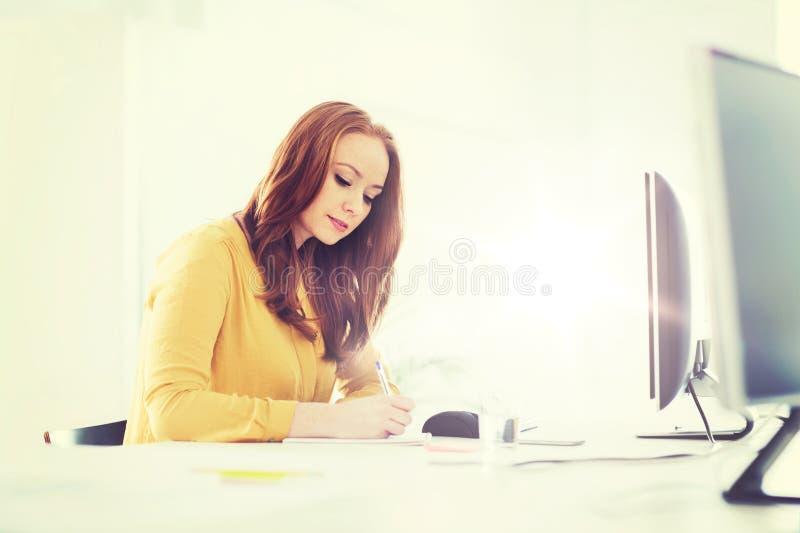 Idérik kvinnlig kontorsarbetare som skriver till anteckningsboken arkivfoton