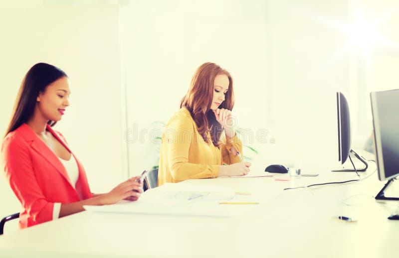 Idérik kvinnlig kontorsarbetare som skriver till anteckningsboken royaltyfri foto