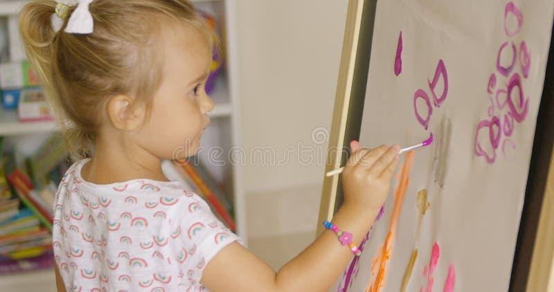 Idérik liten flickamålning i en lekrum royaltyfri bild