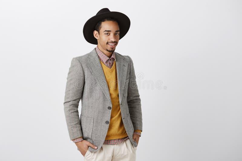 Idérik märkes- diskuterande modeshow Snygg mörkhyad manlig modell i det stilfulla omslaget och hatten, stående halva royaltyfri bild