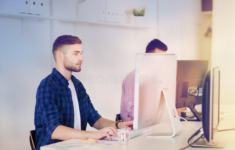 Idérik man eller student med datoren på kontoret royaltyfria bilder