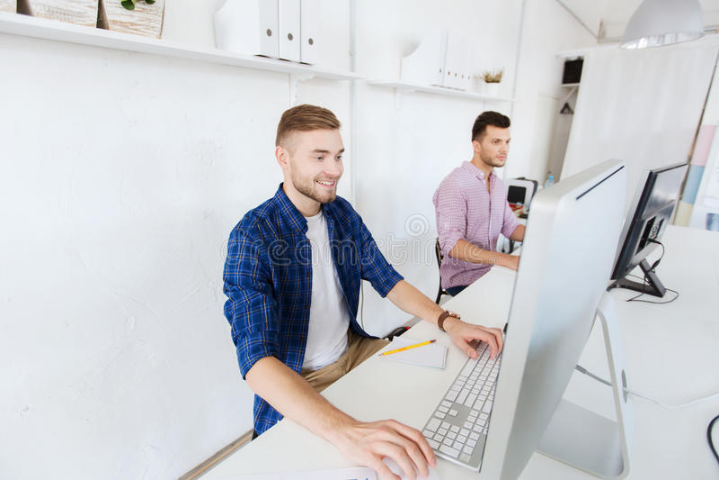 Idérik man eller student med datoren på kontoret royaltyfri foto