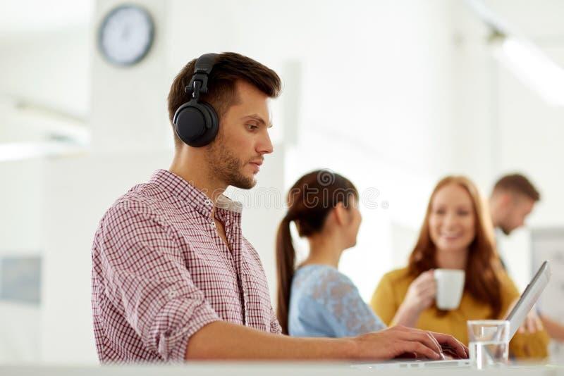 Idérik man i hörlurar med bärbara datorn på kontoret royaltyfria bilder