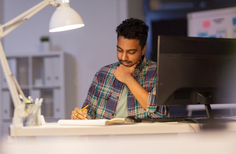 Idérik man med anteckningsboken som arbetar på nattkontoret arkivfoto