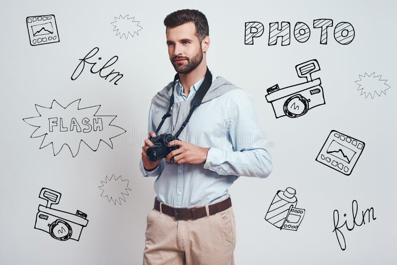 idérik man När du charmar den unga mannen rymmer den digitala kameran och ser bort, medan stå mot grå bakgrund med royaltyfri fotografi
