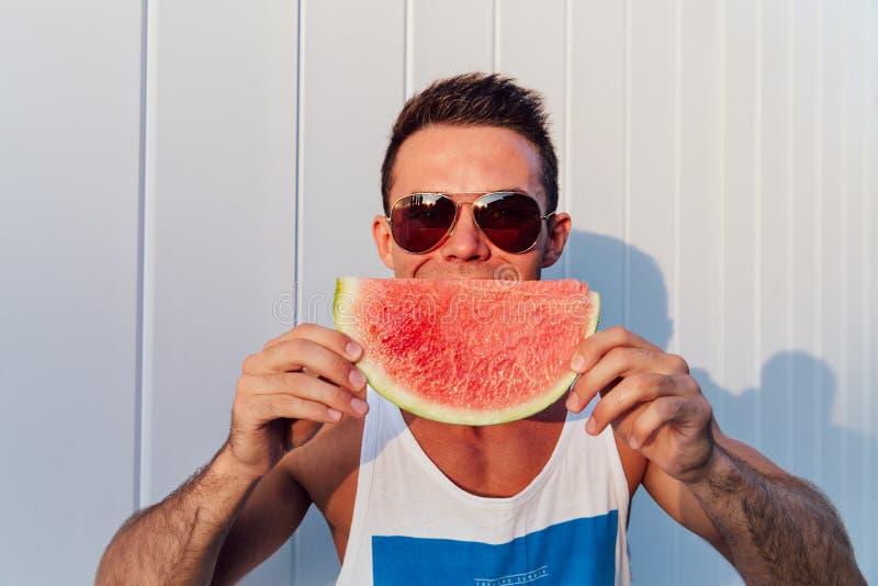 Idérik man som rymmer en vattenmelon, utomhus royaltyfria foton