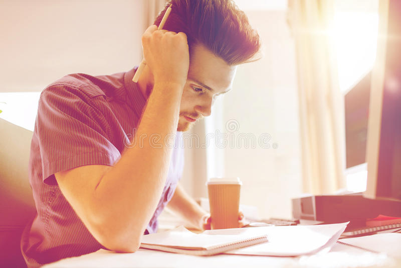 Idérik manlig kontorsarbetare med att tänka för kaffe arkivfoto
