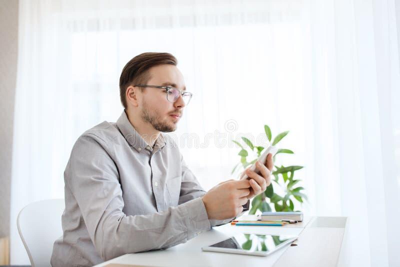 Idérik manlig kontorsarbetare som smsar på smarphone arkivfoton