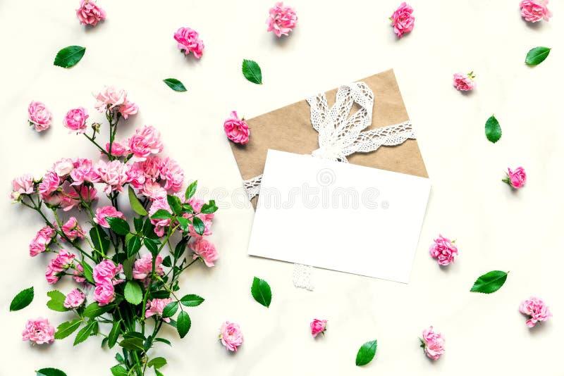 Idérik orientering som göras av rosa färgrosblommor och tomt hälsningkort med kuvertet Lekmanna- lägenhet Åtlöje upp bröllop för  royaltyfria foton
