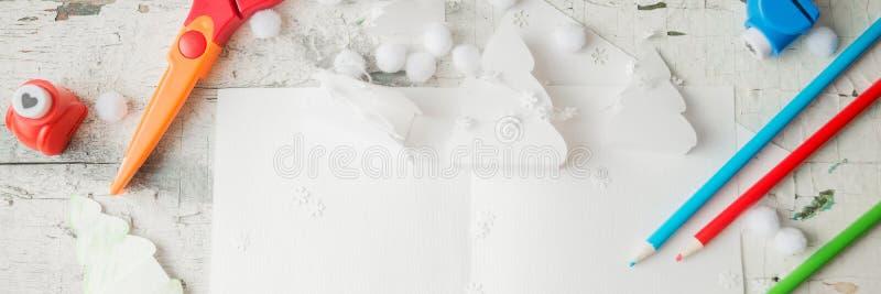 Idérik pappers- julgran på vitbokarket, sax och färgrika färgpennor på bakgrund för färgtabell royaltyfri fotografi