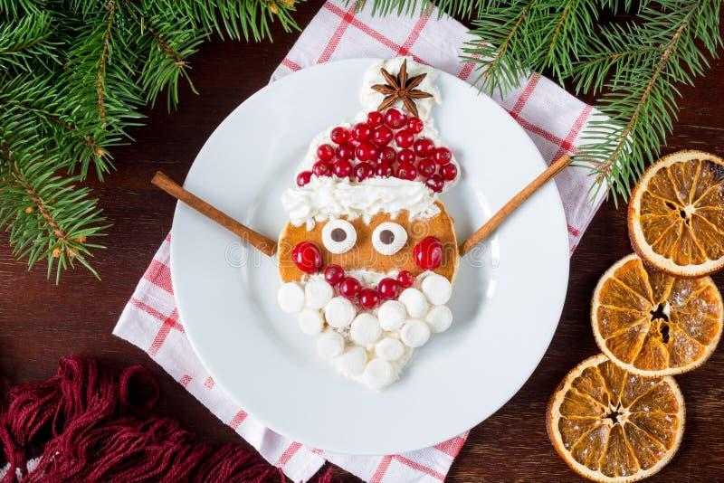 Idérik rolig mat för ungar: gladlynt Santa Claus pannkaka arkivfoto