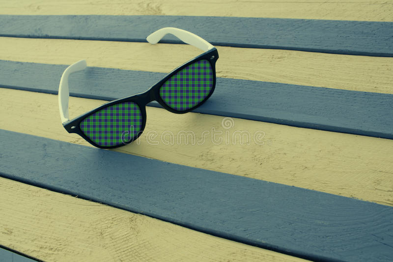 Idérik solglasögon på en randig yttersida arkivfoton