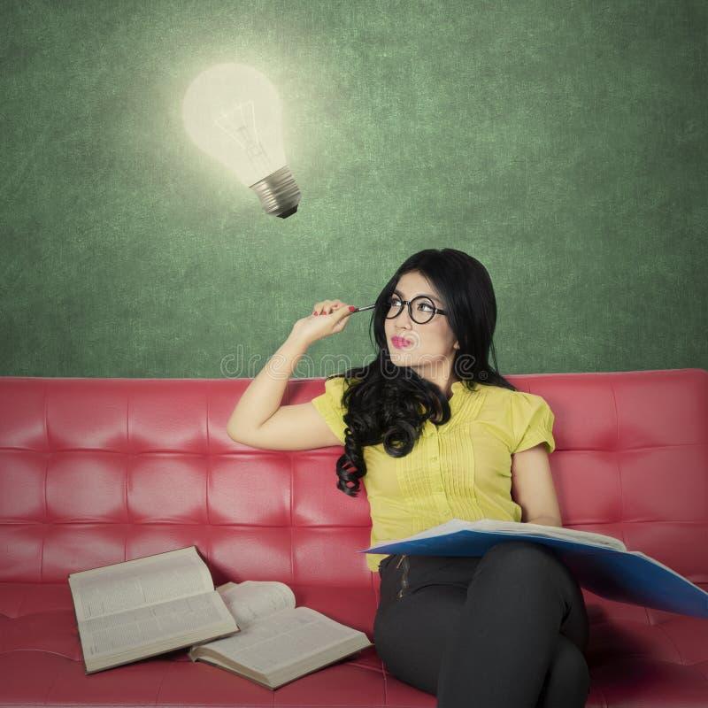 Idérik student som ser den ljusa kulan på soffan arkivfoto