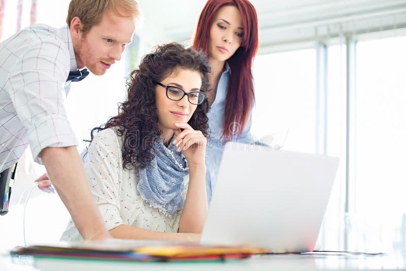 Idérika affärskollegor som i regeringsställning använder bärbara datorn på skrivbordet fotografering för bildbyråer