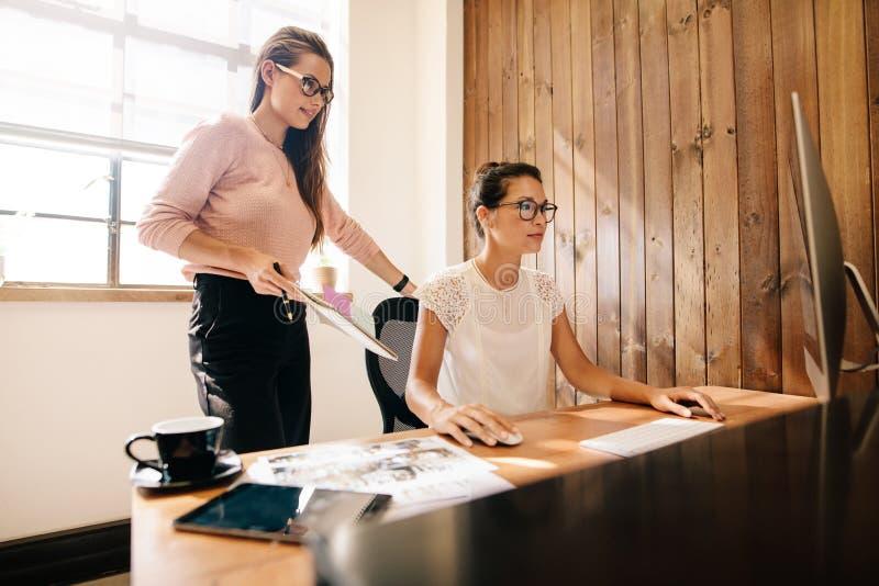 Idérika affärskvinnor på kontorsskrivbordet fotografering för bildbyråer