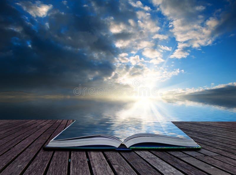 Idérika begreppssidor av boken som bedövar landskap på solnedgångrefl royaltyfri foto