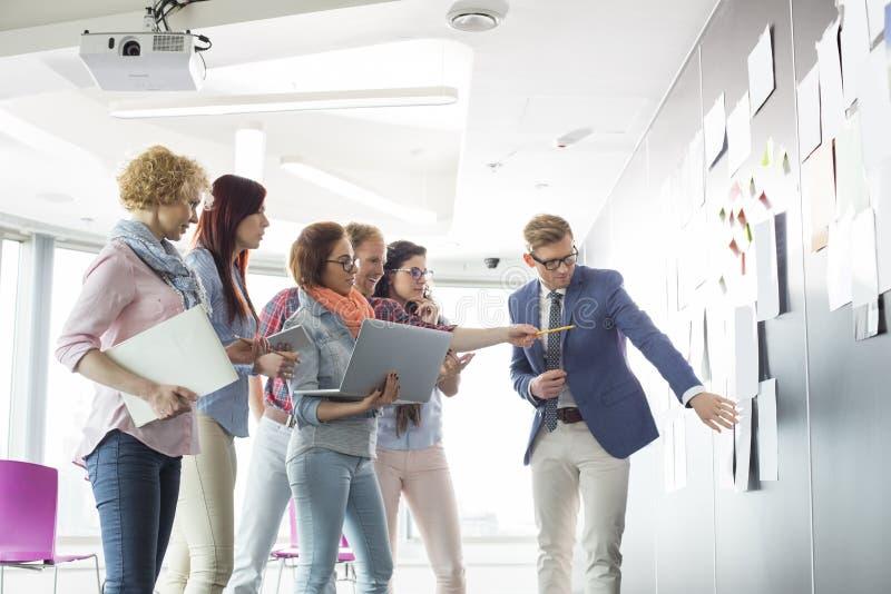 Idérika businesspeople som i regeringsställning diskuterar över dokument på väggen arkivbilder