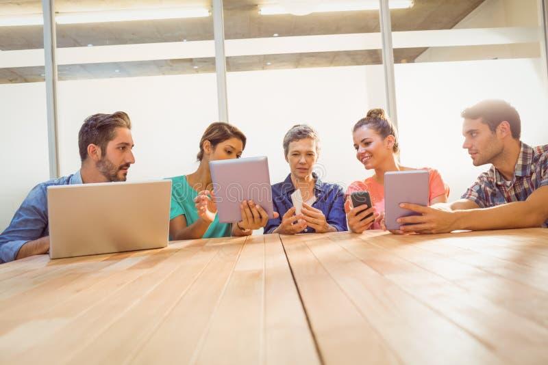 Idérika kollegor med bärbara datorn och den digitala minnestavlan royaltyfri bild