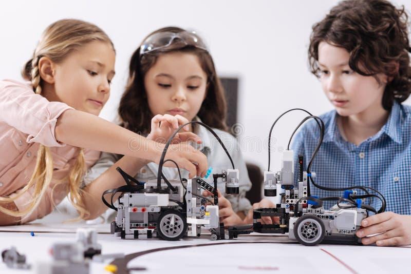 Idérika ungar som arbetar på techprojektet på skolan royaltyfri foto