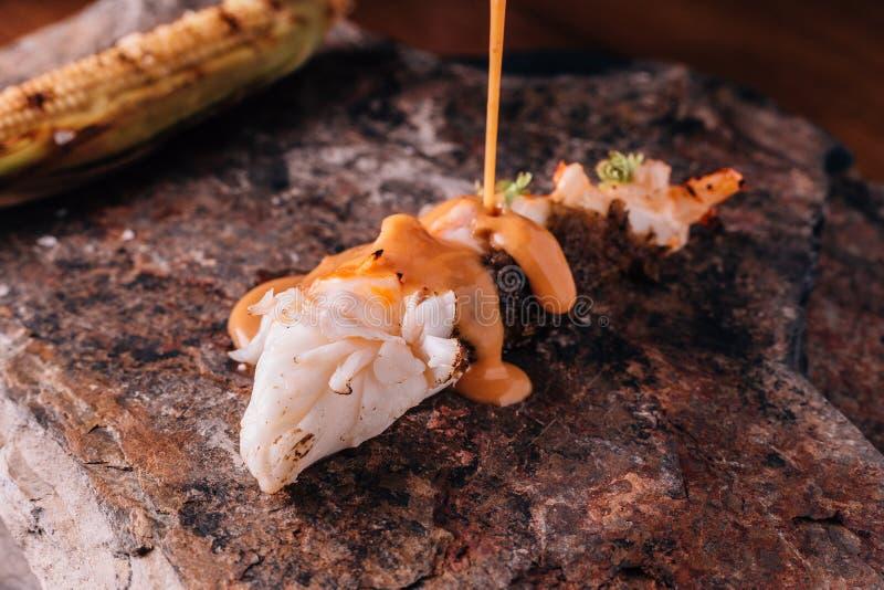 Idérikt äta middag för bot: Grillad hummer som häller med gul curry- och kokosnötdriftstoppsås med grillad havre arkivfoto