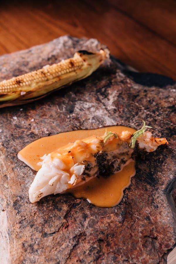 Idérikt äta middag för bot: Grillad hummer som häller med gul curry- och kokosnötdriftstoppsås med grillad havre arkivbilder
