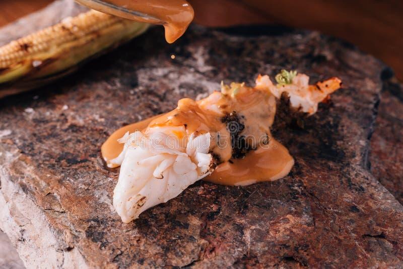 Idérikt äta middag för bot: Grillad hummer som häller med gul curry- och kokosnötdriftstoppsås med grillad havre royaltyfri foto