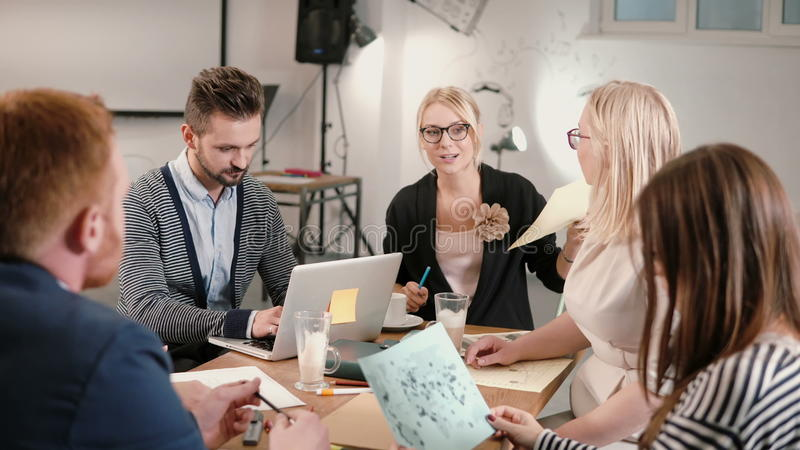 Idérikt affärslag på tabellen i ett modernt startup kontor Den kvinnliga ledaren förklarar detaljerna av projektet royaltyfri fotografi