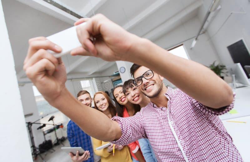 Idérikt affärslag som tar selfie på kontoret royaltyfria bilder