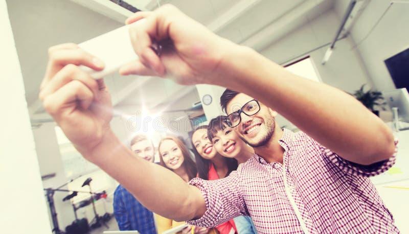 Idérikt affärslag som tar selfie på kontoret royaltyfri fotografi
