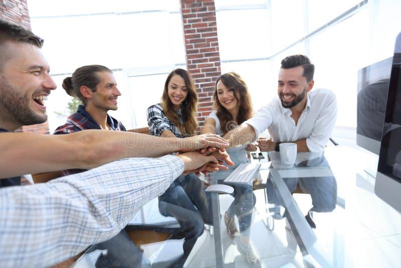Idérikt affärslag som tillsammans sätter händer på kontoret royaltyfri fotografi