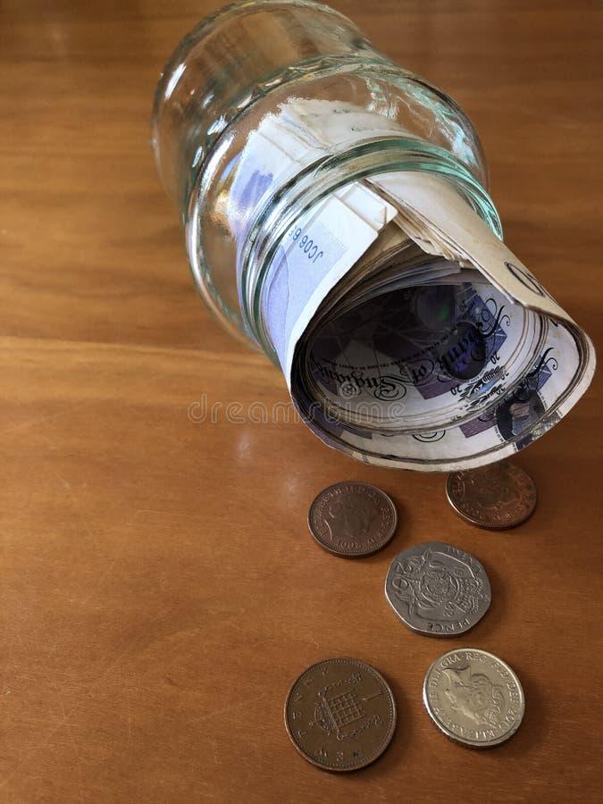 Idérikt begrepp, sparande pengar i en driftstoppkrus arkivfoto
