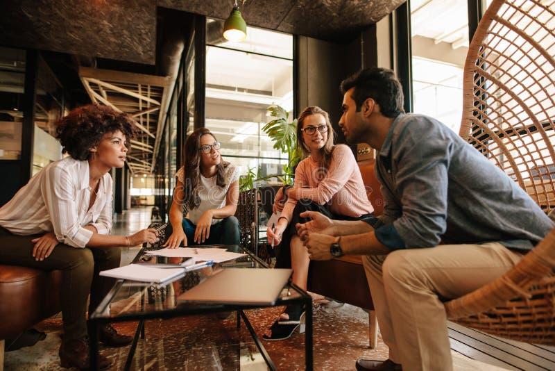 Idérikt folk som har ett möte i modernt kontor arkivfoto