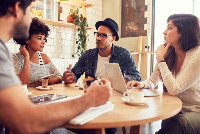 Idérikt folk som möter på ett kafé royaltyfri bild