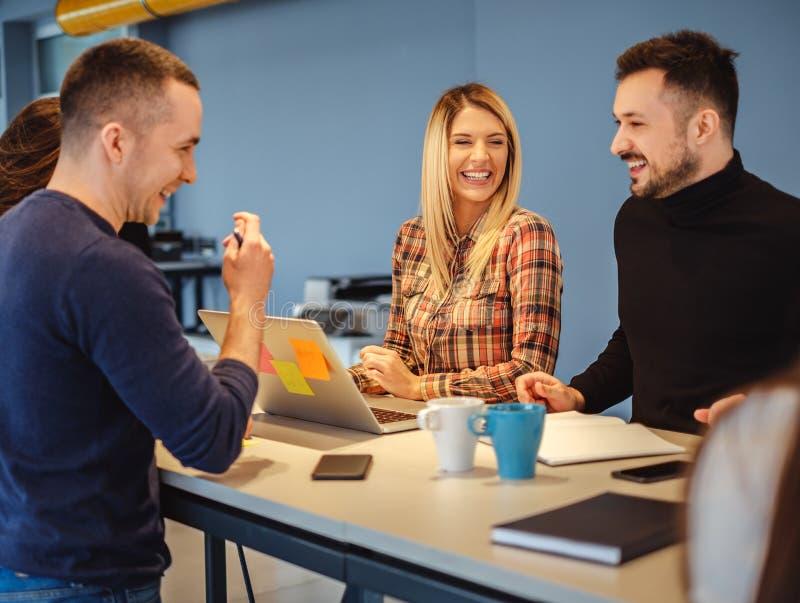Idérikt folk som skrattar på kontorsmötet royaltyfri bild