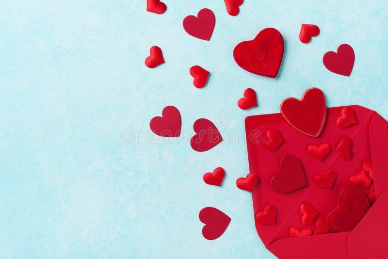 Idérikt kort för valentindaghälsning med det öppnade kuvertet och röda hjärtor arkivbild