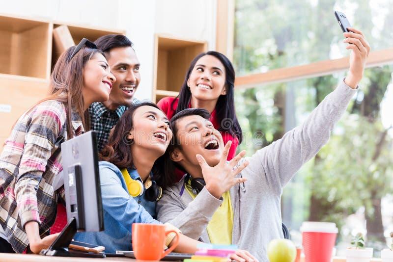Idérikt lag av fem entusiastiska anställda som gör en selfiepho royaltyfri bild