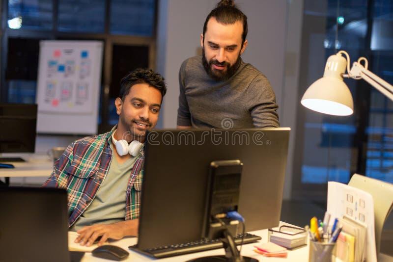 Idérikt lag med datoren som sent arbetar på kontoret arkivbilder