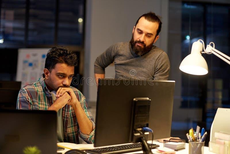 Idérikt lag med datoren som sent arbetar på kontoret royaltyfri fotografi