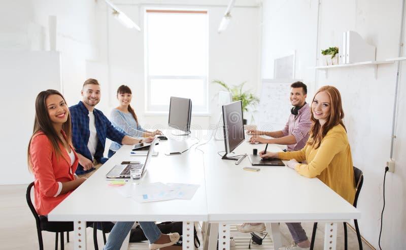 Idérikt lag med datorer, ritning på kontoret royaltyfria foton