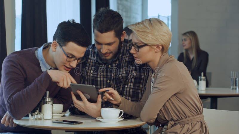 Idérikt lag som använder smartphonen och talar i tillfälligt kontor arkivfoto